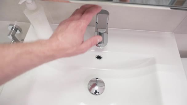 Male hand turning water tap for pouring water into sink in bathroom. Flowing water. Adult man turning off tap. Top view.