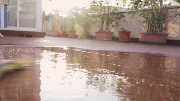 Sommerheißer Tag im Hinterhof - ein Mann wäscht barfuß eine Fliesenterrasse