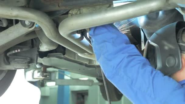 Mechanic cuts off the muffler in the car