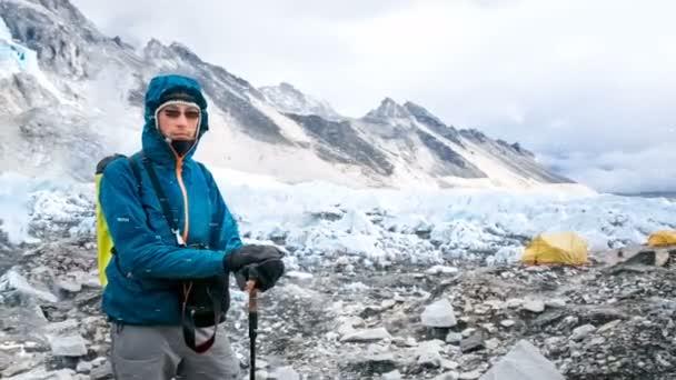 Mladý muž v modrém saku odpočívá po horolezectví