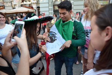 Moscow, Russia - June 23, 2018: Mexican football fan collects autographs on his national country flag. The Nikolskaya streets in Moscow, FIFA world cup, Mundial 2018