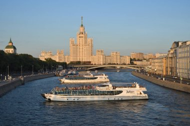 Moscow, Russia - June 23, 2018: View from Zaryadye Park Moskvoretskaya Embankmentand, Moscow river with cruise ships and Stalinist skyscraper House on Kotelnicheskaya Embankment