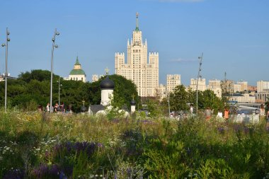 Moscow, Russia - June 23, 2018: People relax in Zaryadye Park near Moscow Kremlin. Scenic view on the Stalinist skyscraper House on Kotelnicheskaya Embankment