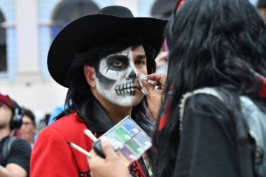 Moscow, Russia - June 29, 2018: The girl participant makes the sugar skull makeup on face a man during Dia de los Muertos Mexican carnival. Day of The Dead