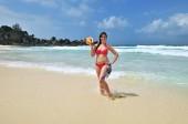 Fotografie Junge gegerbt Mädchen mit großen Schale steht am Strand und nimmt ein Sonnenbad gegen azurblauen Ozean. Anse Cocos Beach. Tropischen Urlaub. Seychellen