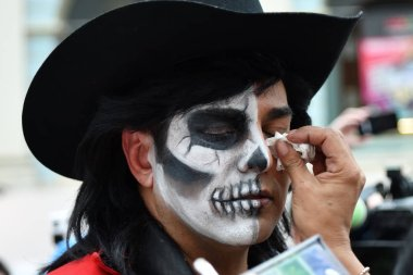 Moscow, Russia - June 29, 2018: A participant makes the sugar skull makeup on face a man during Dia de los Muertos Mexican carnival. Day of The Dead