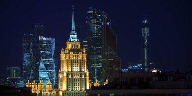 Moscow, Russia - June 27, 2018: Moscow night skyline. Stalinist skyscraper on the background of the Moscow City business centre skyscrapers shown at night. Capital of Russia