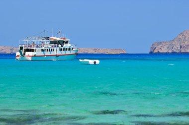 Small cruise ship and boat shown in Balos lagoon, Crete, Greece