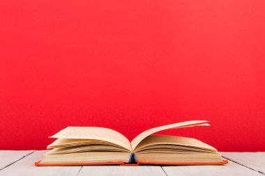education and wisdom concept - open book on wooden table, red background