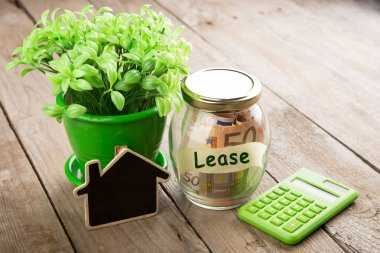 Real estate finance concept - money glass with Lease word and vintage key