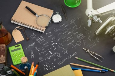 Education concept - books, microscope and Science sketch on the blackboard