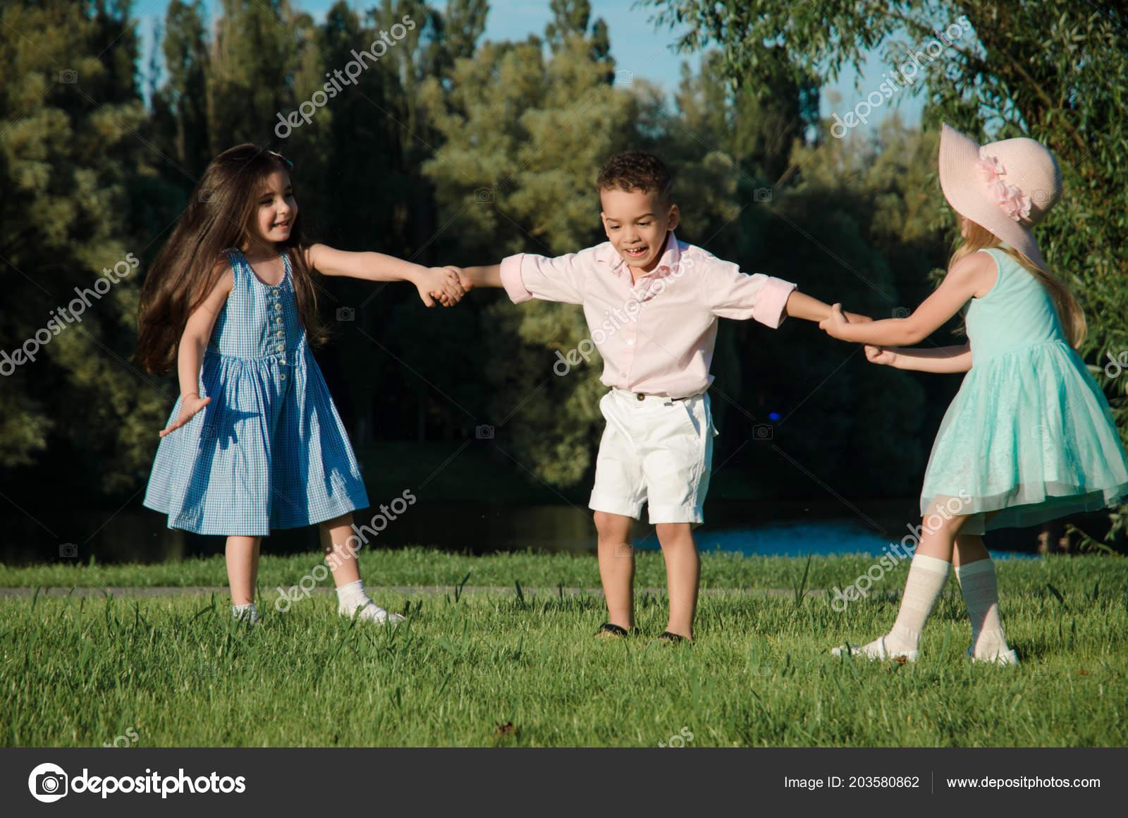 a5503e5c6d6 Μικρά Παιδιά Έπαιζαν Στο Γρασίδι Δύο Κορίτσια Και Ένα Αγόρι ...