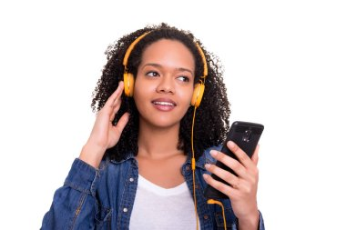 Beautiful young african american woman holding smartphone and listening to music in headphones isolated on white background