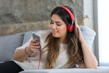 Beautiful young woman relaxing on couch while listening to some music