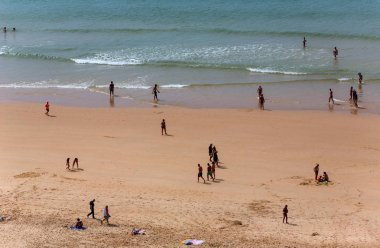 People at the famous beach of Praia da Rocha in Portimao. This beach is a part of famous tourist region of Algarve.