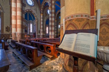 ALBA, ITALY - JUNE 14, 2020: Holy book on the stand as wooden pews and columns on background inside of San Lorenzo - a Roman Catholic cathedral aka Duomo dedicated to Saint Lawrence in small town of Alba in Piedmont, Northern Italy.