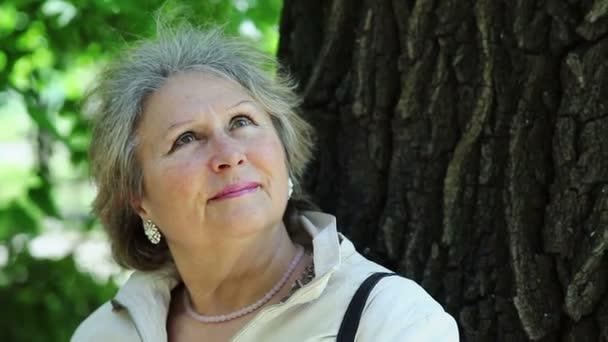 Közelkép idősebb nő a szabadban a parkban felnézett
