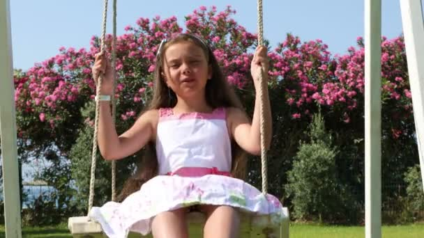 Adorable little girl in white dress swinging on a swing in the city park