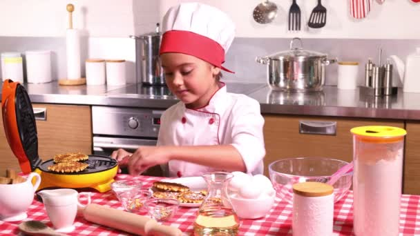 Pretty little girl in a chef suit cooks waffles in the kitchen at home