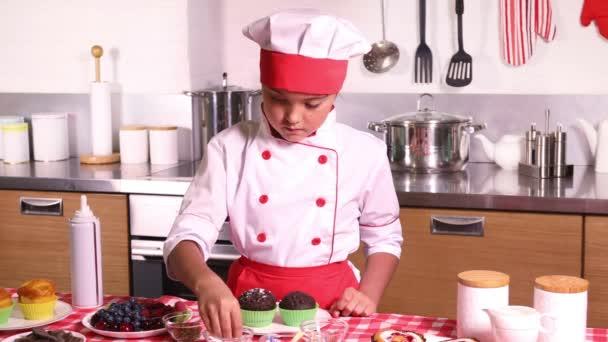 Kis lány szakács ruha díszíti egy cupcake bogyó otthon a konyhában