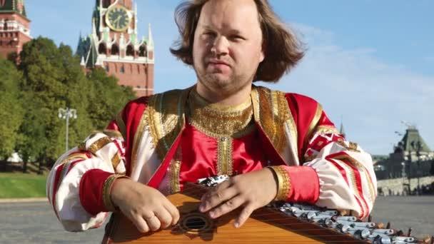 Umělec v tradiční ruské oblečení hraje hudební nástroj gusli staré ruské na pozadí Kremlu na Rudém náměstí. Moskva, Rusko