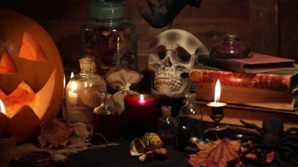 Podzimní Zátiší s Halloween dýně, lebka, staré knihy, javorové listy, archivní vína a svíčky na staré dřevěné pozadí