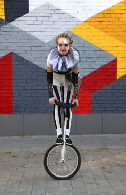 Girl clown in circus clothes performing with a unicycle outdoor