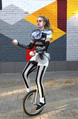 Girl clown rides a unicycle and juggles balls outdoor