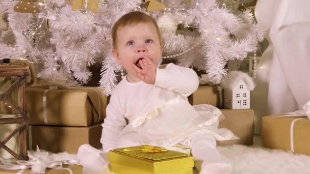 Kleines Mädchen (acht Monate alt) in einem weißen Kleid sitzt unter einem Weihnachtsbaum mit Geschenken