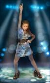 Una bambina vestita in stile discoteca ballando sul palco nella Spotlight