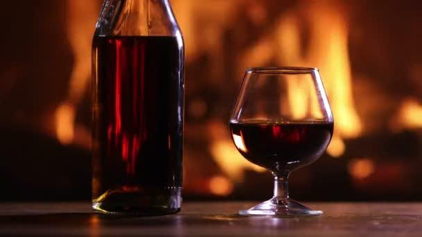 Egy üveg pálinkát és egy üveg van, szemben az égő tűzhely az asztalra