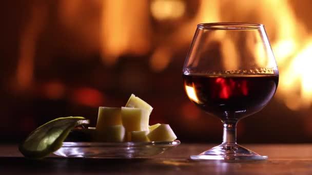 Egy pohár pálinka és a sajtot és a citromos tányér van az asztalon, a háttérben egy égő tűzhely