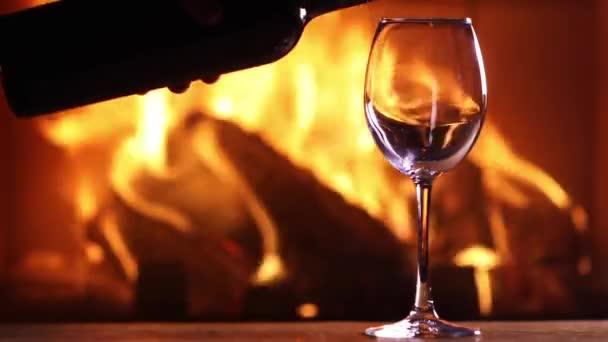 Die Hand eines Mannes gießt Rotwein aus einer Flasche in ein Glas auf dem Hintergrund eines brennenden Kamins