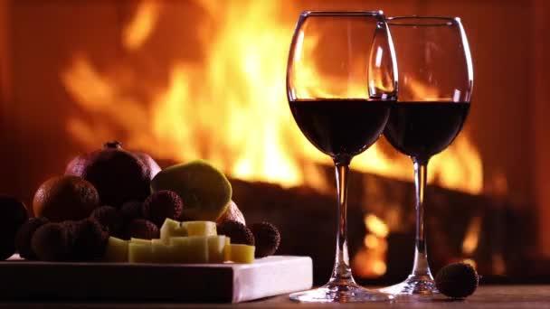 zwei Gläser Wein und ein Teller mit Obst und Käse auf dem Hintergrund eines brennenden Kamins