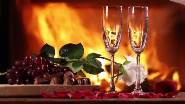 Sekt in Gläser auf dem Hintergrund eines brennenden Kamins gießen. Neben einem Glas Sekt auf dem Tisch stehen Teller mit Trauben, Schokolade und weißer Rose