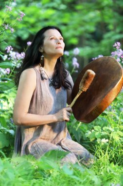Shamanic woman playing on shaman frame drum at dawn in the forest on background with leaves and flowers