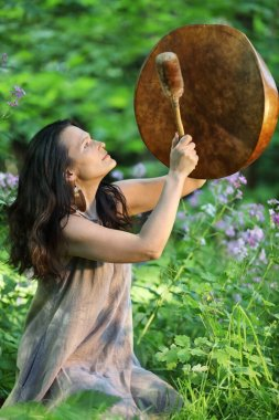 Shaman woman playing her shaman sacred drum in the forest on background with leaves and flowers. Ethnic tradition