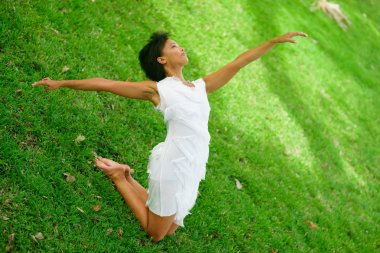 A beautiful African-looking girl with black short hair in a dancing pose dressed in a white dress on a grass