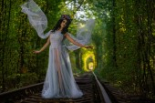 Fotografie make up of dead bride dressed in wedding clothes in the tunnel inside a forest with train rails