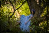Fotografie make up of dead bride with black hair dressed wedding clothes lieng on the tree in the forest