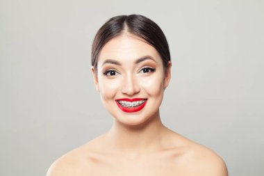 Attractive brunette woman in braces smiling on white background