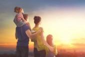 šťastná rodina při západu slunce. otec, matka a dcery dvě děti baví a hraje v přírodě. dítě sedí na ramena svého otce.