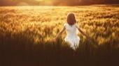 Ein fröhliches Kind hat im Sommer Spaß an der Natur. Kind spielt auf der Wiese im Hintergrund des Sonnenuntergangs. Mädchen läuft auf Getreidefeld und berührt Weizenähren.