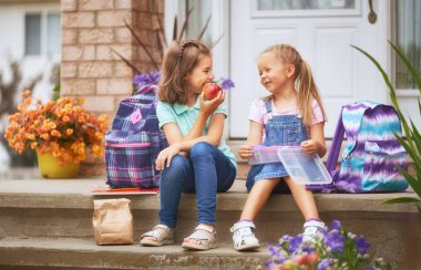Pupils of primary school with lunch-boxes in hands. Girls with backpacks are eating fruit near building outdoors. Beginning of lessons. First day of fall.