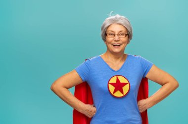 Joyful beautiful senior woman in superhero costume posing on turquoise background. stock vector