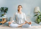 Fotografie Glückliche junge Frau genießt sonnigen Morgen und praktiziert Meditation auf dem Bett.