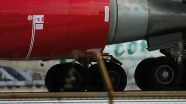 Detail kola a motor letadla pojíždění před odletem z letiště v Phuketu