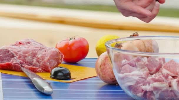Mann schneidet Fleisch für Grill