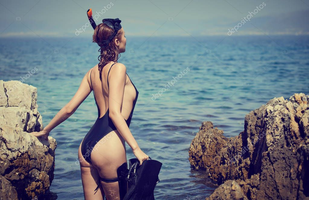 Adventure. Woman traveler and explorer in sea cave, shining a flashlight into the chest searching fish