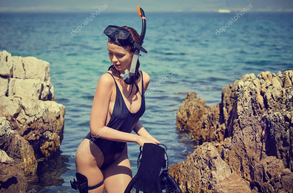 Sexy beach bikini girl wearing scuba gear and crossbow